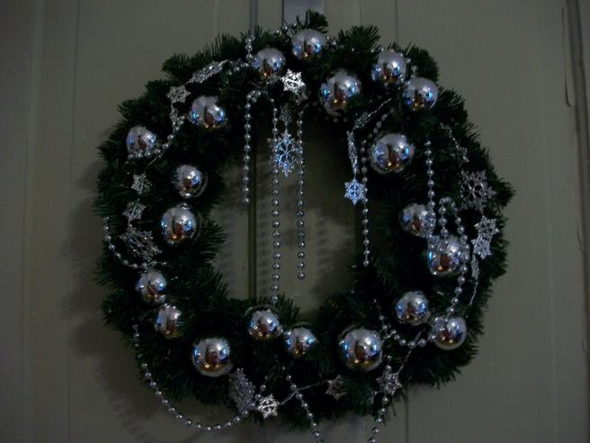 Wreath I made for my front door a few years ago.  I bought a simple green wreath at Michael's and embellished it with Dollar Store ornaments and bead garland.  Used a hot glue gun and just started gluing.  I thin it turned out ok.